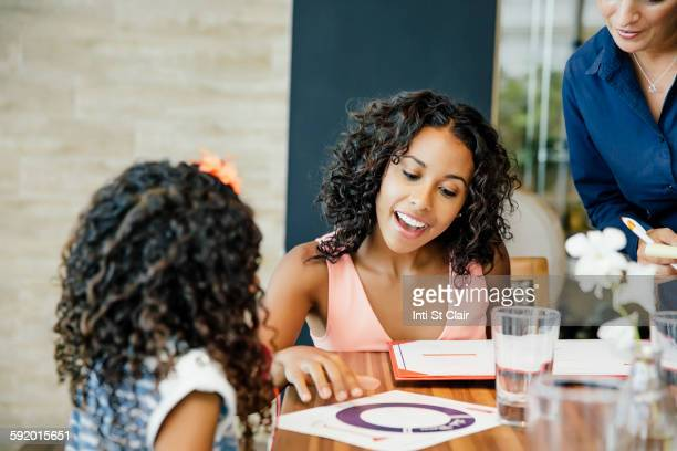 Mother and daughter reading menu restaurant table