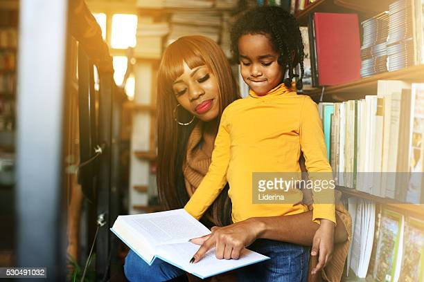 African mother and daughter reading together in library. Focus on little girl.