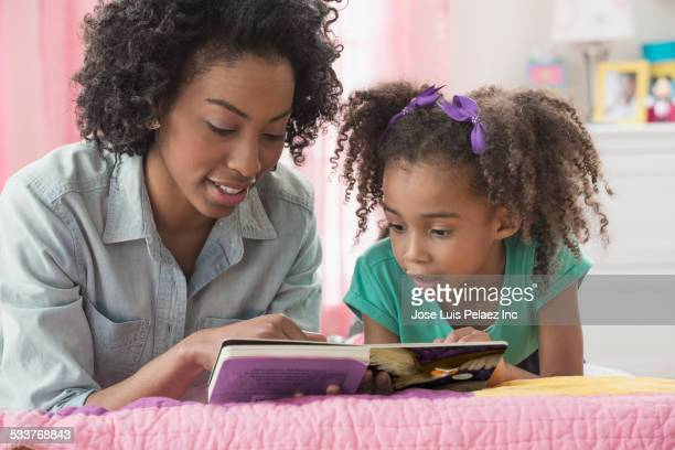Mother and daughter reading together on bed