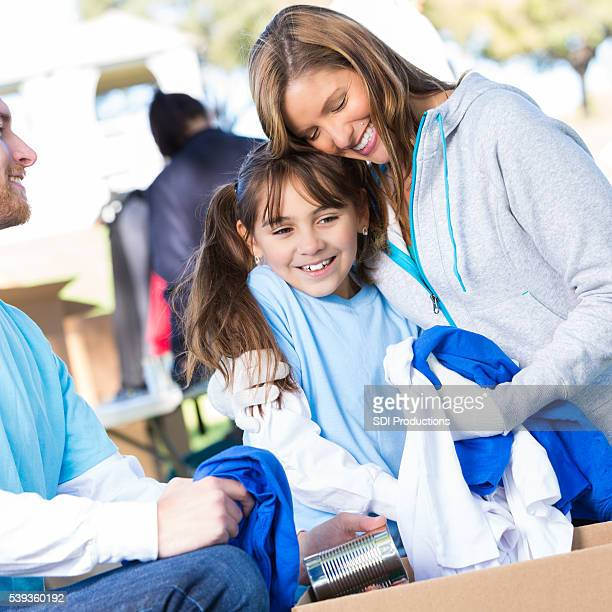 Mother and daughter receiving clothing at charity drive