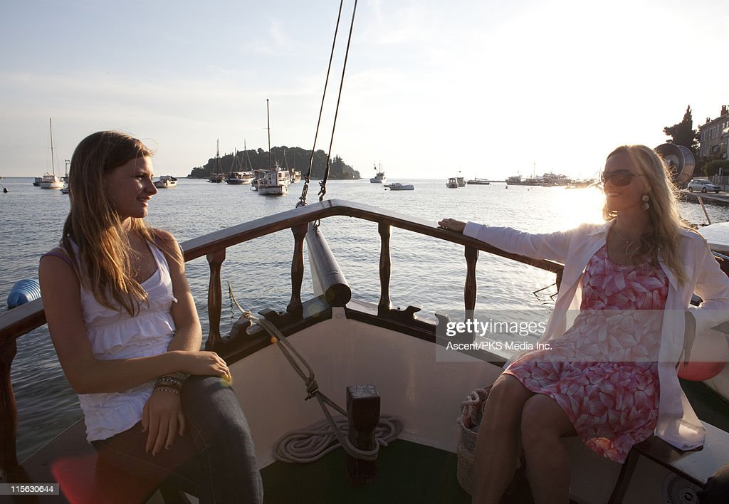 Mother and daughter relax/converse in boat bow : Stock Photo