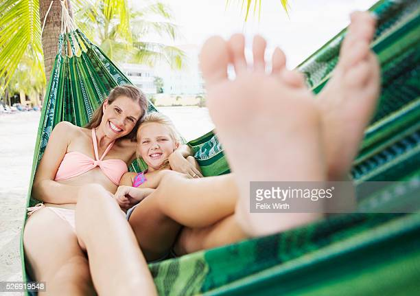 Mother and daughter (10-12) relaxing in hammock on beach