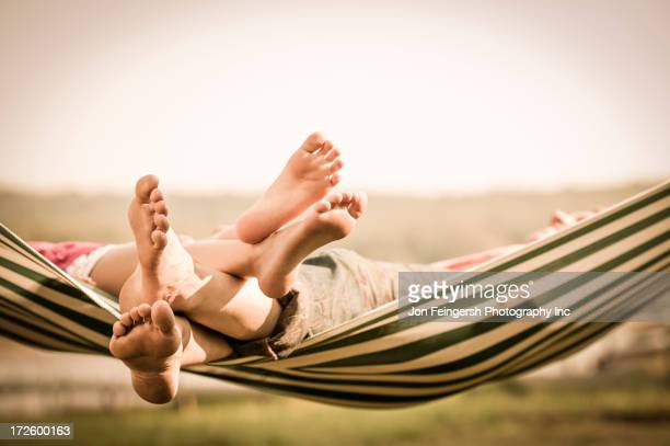 Mother and daughter relaxing in hammock outdoors