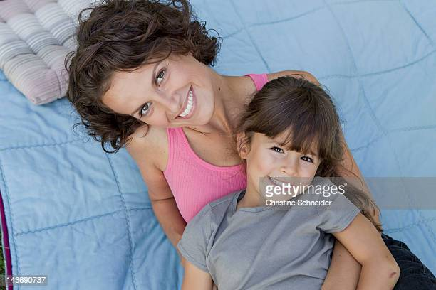 Mother and daughter relaxing on blanket