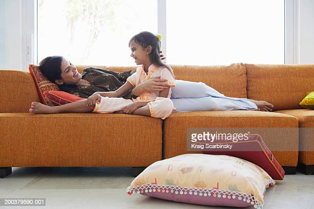 Mother and daughter (7-9) relaxing on sofa, smiling