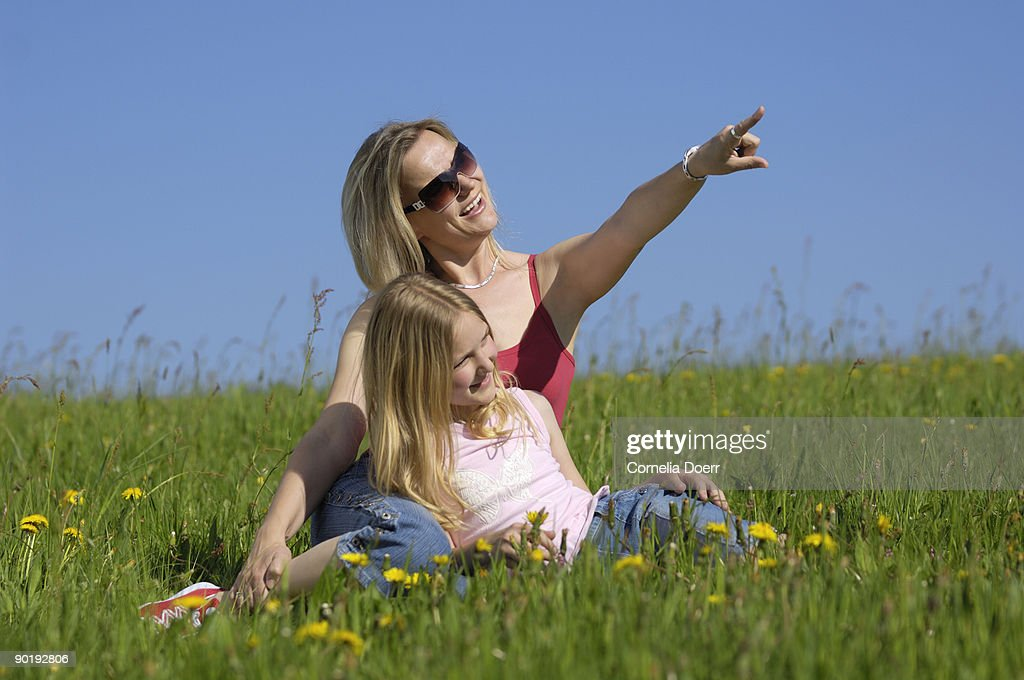 Mother and daughter resting in meadow : Stock Photo