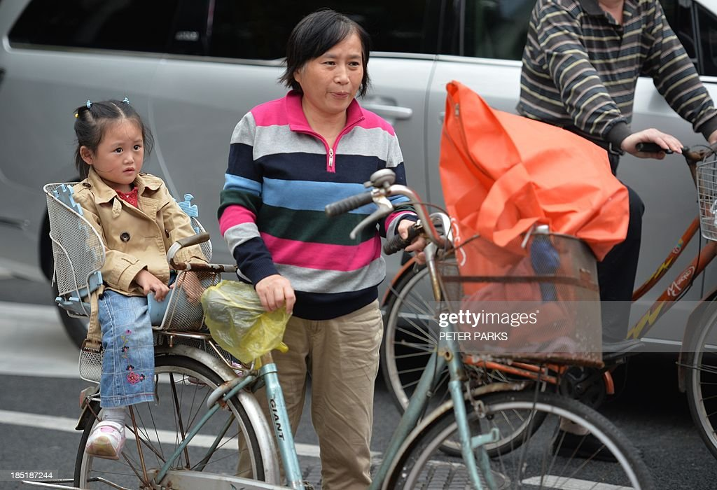 A mother and daughter ride a bike through a commercial district of Shanghai on October 18, 2013. China's economy expanded 7.8 percent year-on-year in July-September, data showed, snapping two quarters of slowing growth, but analysts questioned whether the improvement was sustainable. AFP PHOTO/Peter PARKS