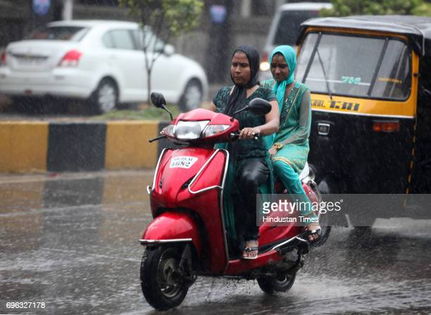 Mother and daughter ride through the heavy rain experienced in the city today