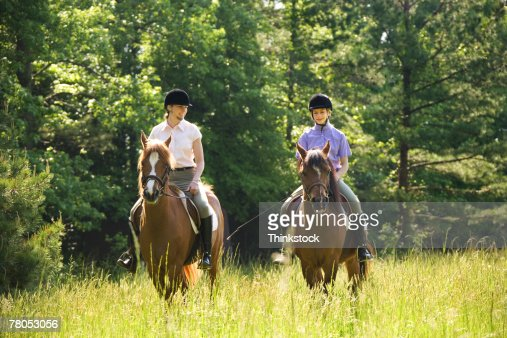 Mother and daughter riding horses
