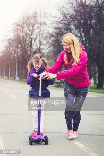 Mother and daughter riding on a push scooter : Stock Photo