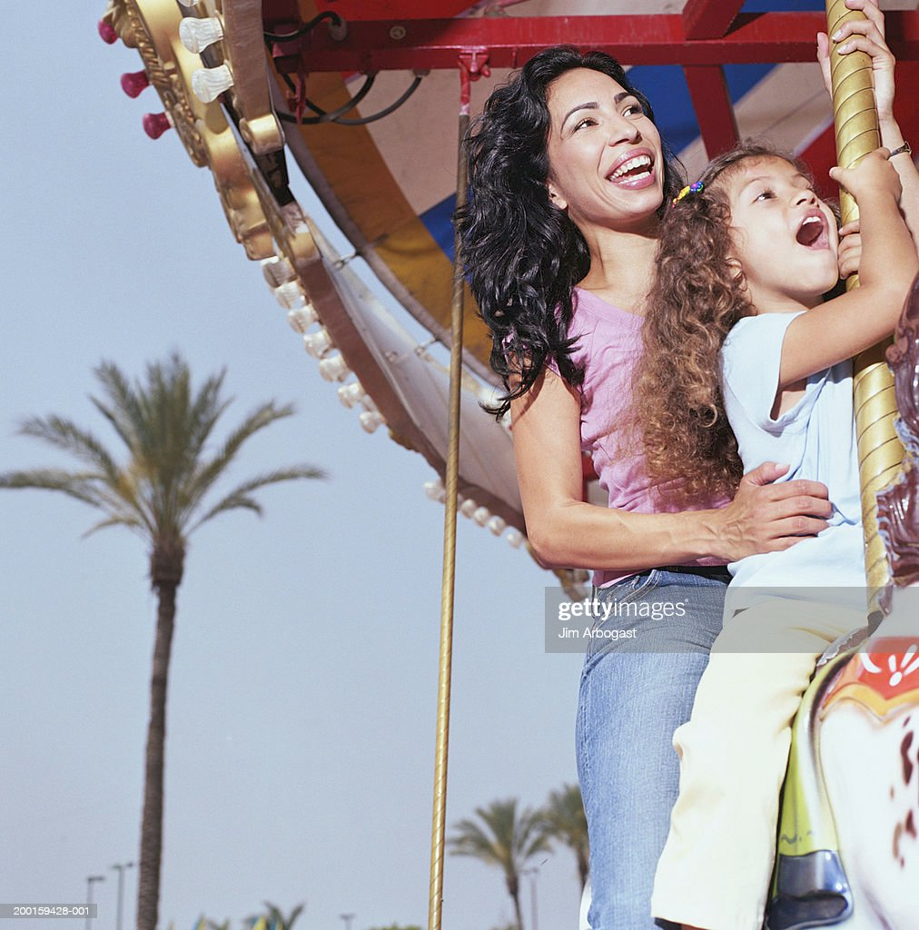 Mother and daughter (3-5) riding on carousel, smiling : Stock Photo