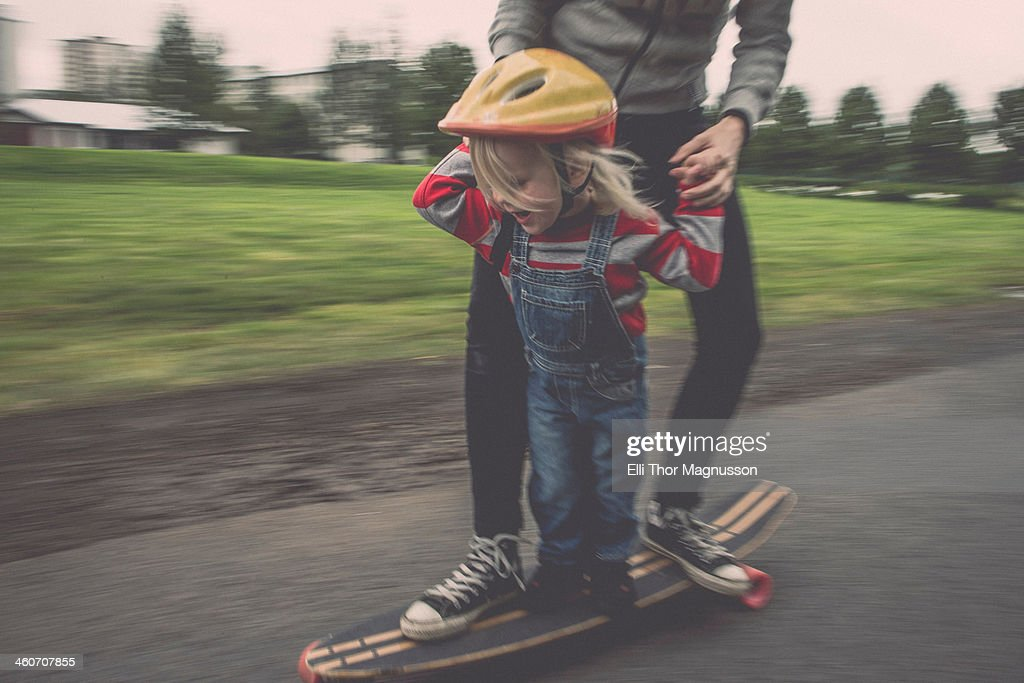 Mother and daughter riding on skateboard in park : Stock Photo