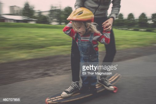 Mother and daughter riding on skateboard in park