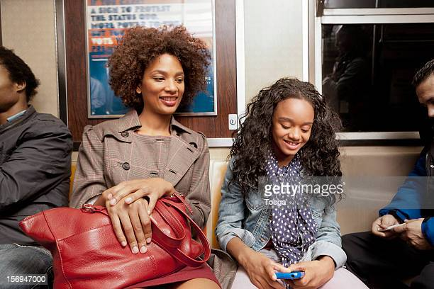 Mother and daughter riding subway