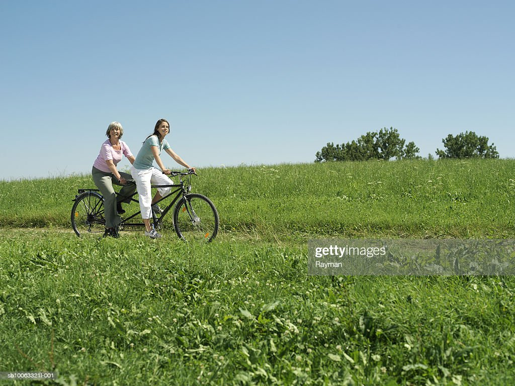 Mother and daughter (16-17) riding tandem bicycle in meadow : Stock Photo