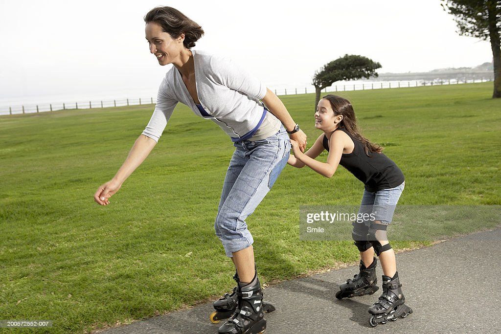 Mother and daughter (8-10) rollerblading in park