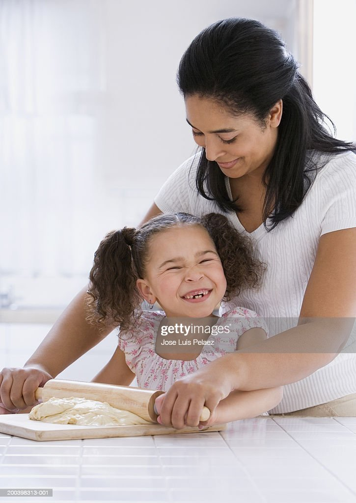 Mother and daughter (4-6) rolling dough, smiling : Stock Photo