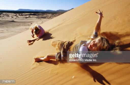 Mother and daughter rolling down sand dunes, Coral Pink Sand Dunes State Park, United States of America : Stock Photo