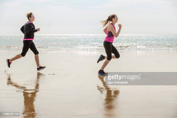 Mother and daughter running on beach, Folkestone, UK