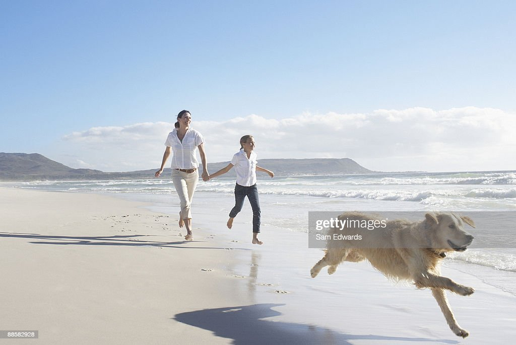 Mother and daughter running on beach : Stock Photo