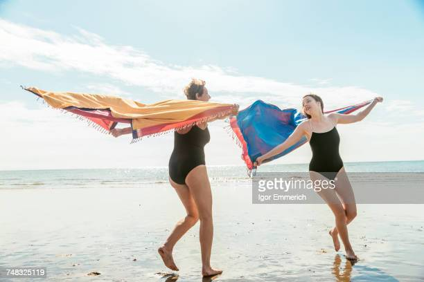 Mother and daughter running on beach with shawls in air, Folkestone, UK