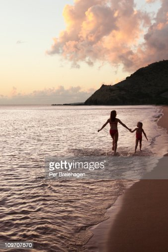 Mother and daughter running on Caribbean beach