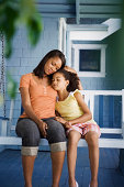 Mother and daughter seated on porch swing