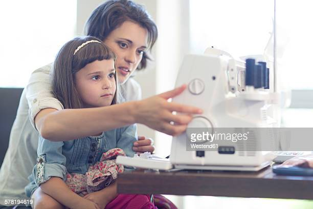 Mother and daughter sewing clothes at home