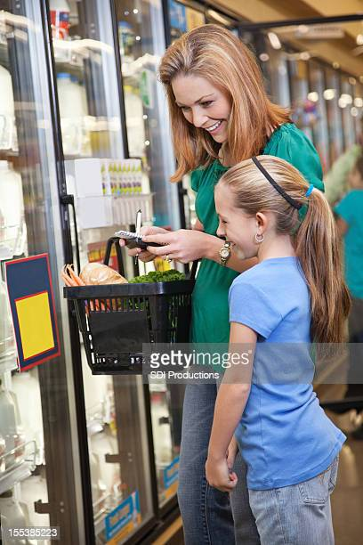 Mother and daughter shopping at the grocery store together