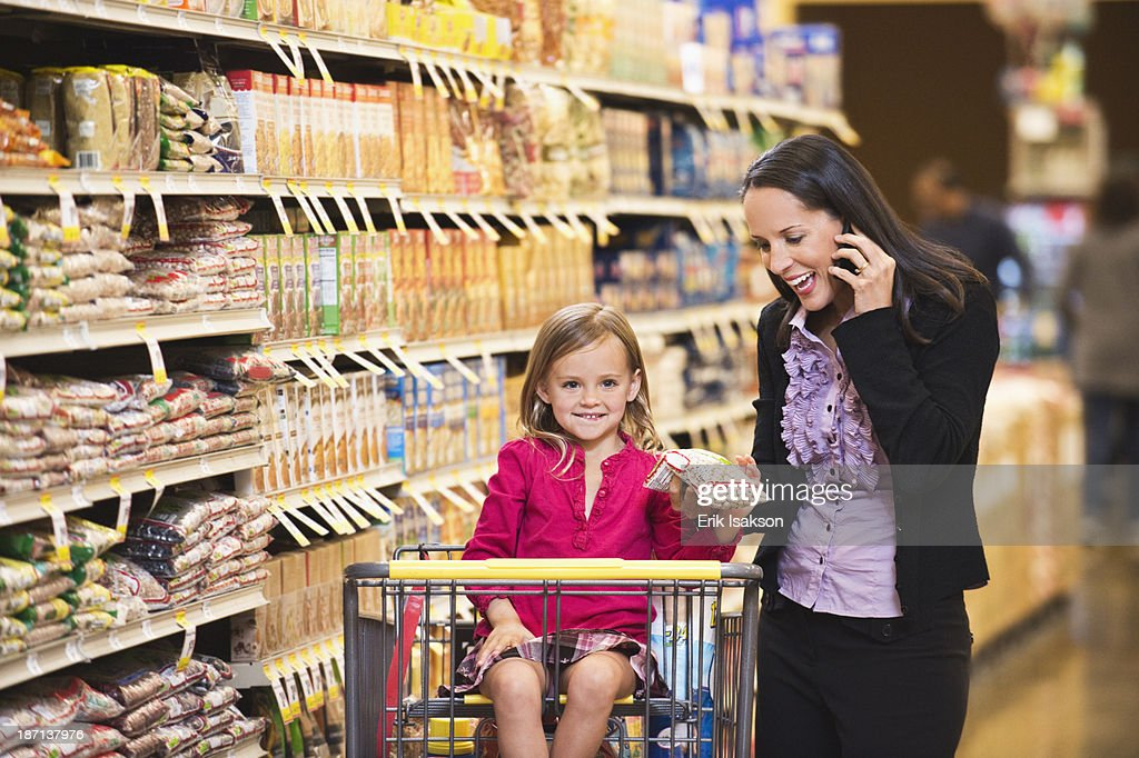 Mother and daughter shopping in grocery store : Stock Photo
