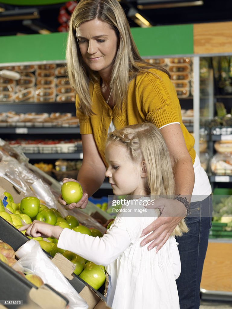 Mother and daughter shopping in supermarket  : Stock Photo