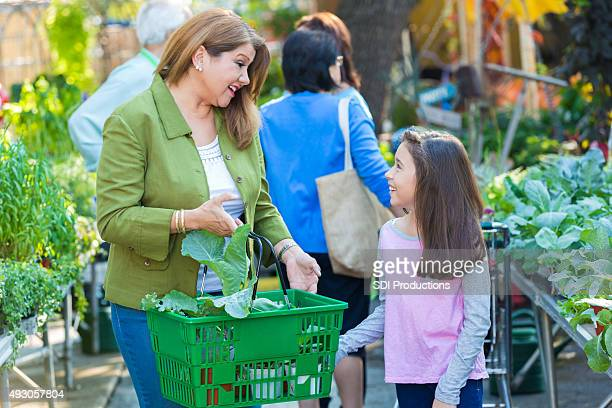 Mother and daughter shopping together at gardening store or nursery