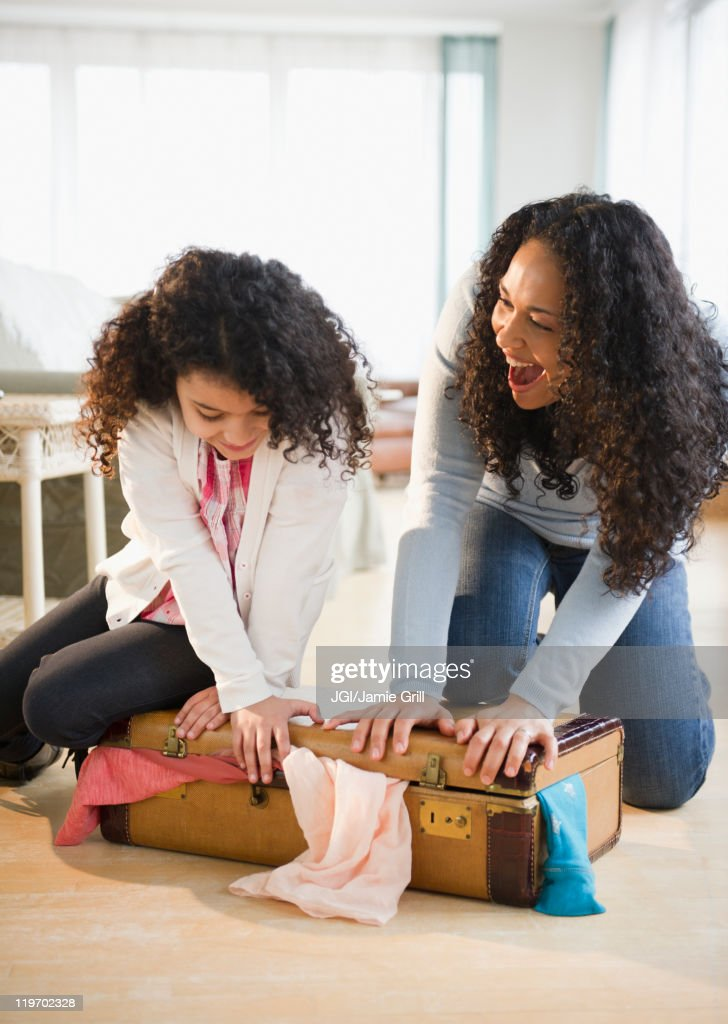 Mother and daughter shutting suitcase : Stock Photo
