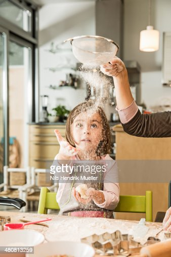 Mother and daughter sieving flour in kitchen