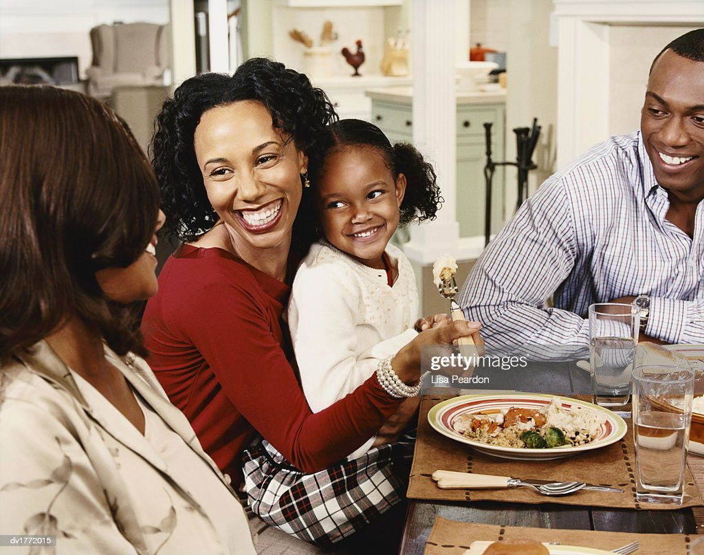 Mother and Daughter Sit at a Table With Friends Eating a Roast Dinner : Stock Photo