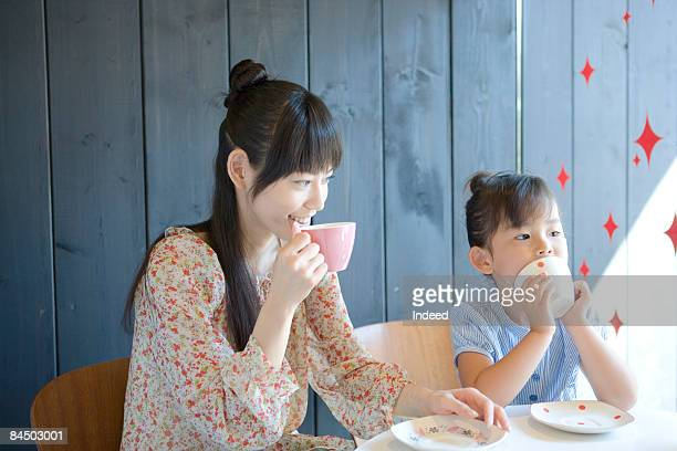 Mother and daughter sitting and drinking tea