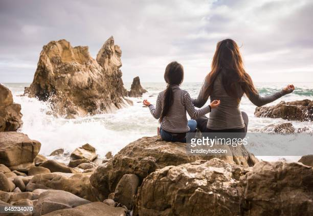 Mother and daughter sitting and meditating on rocky beach together