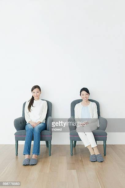 Mother and daughter sitting armchair