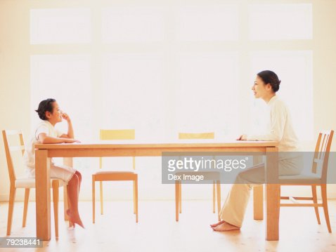 Mother and daughter sitting at opposite ends of table, profile : Stock Photo