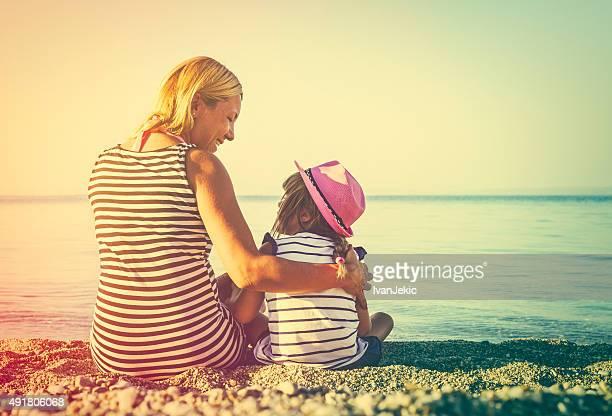 Mutter und Tochter sitzen am Strand bei Sonnenuntergang zusammen