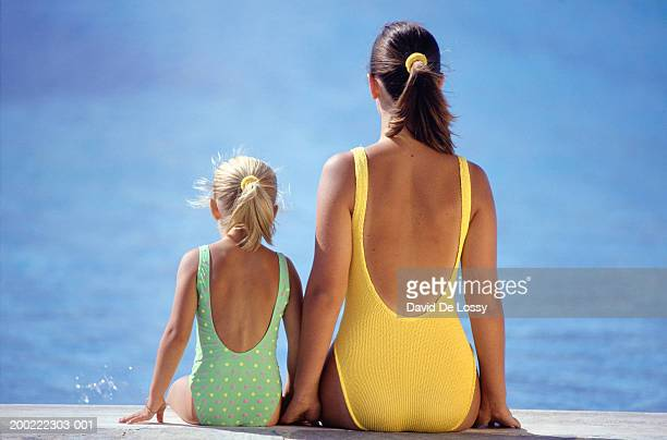 Mother and daughter (6-7) sitting by pool, rear view