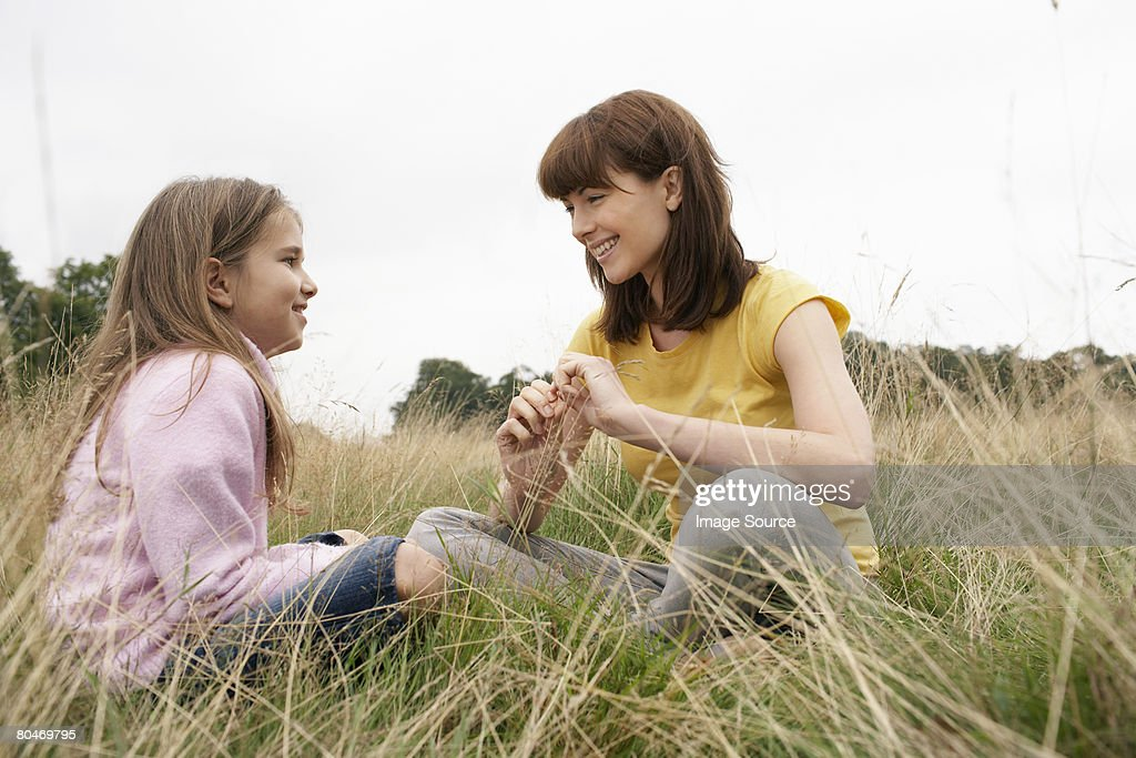 Mother and daughter sitting in a field : Stock Photo