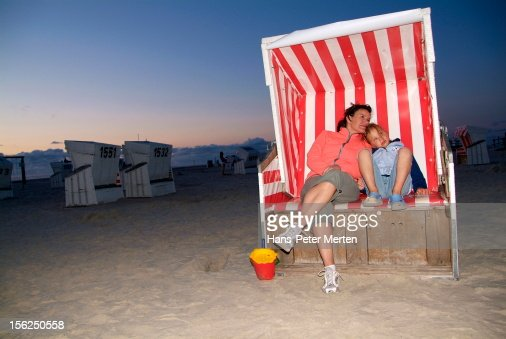 mother and daughter sitting in beach chair : Stock Photo