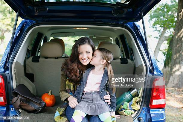 Mother and daughter (6-7) sitting in car trunk