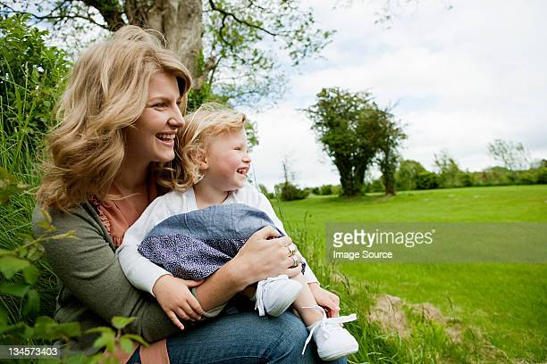 Mother and daughter sitting in field, looking away