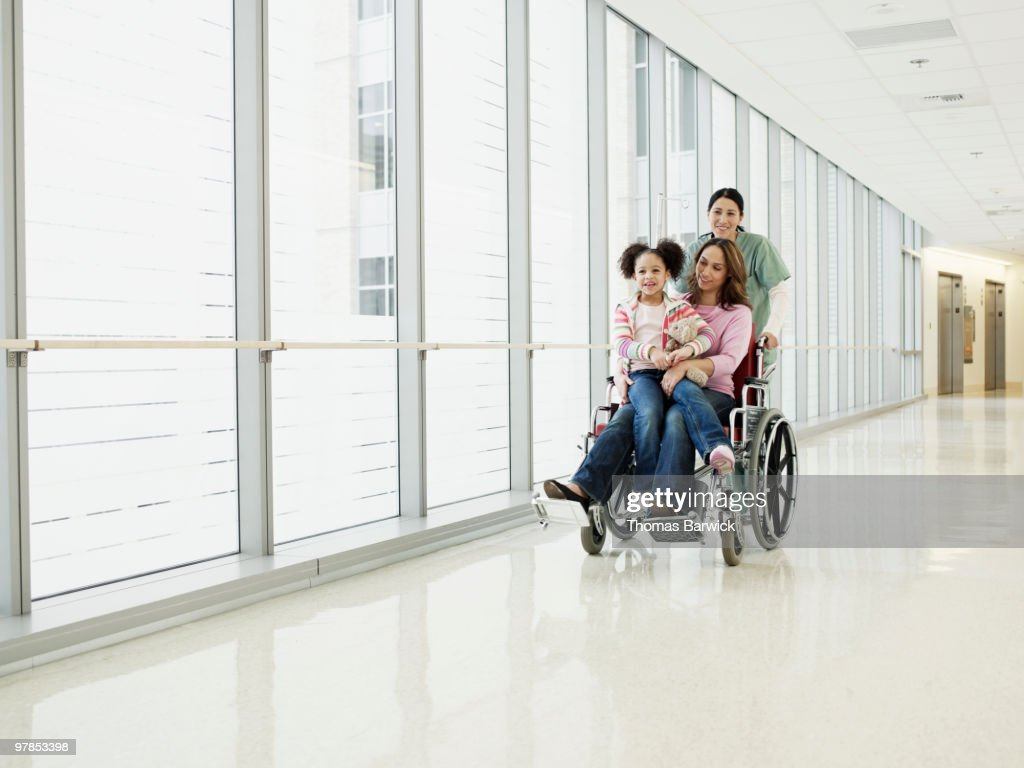 Mother and daughter sitting in wheelchair : Stock Photo