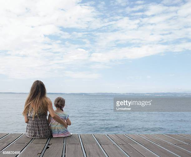 Mother and daughter sitting on a landing stage