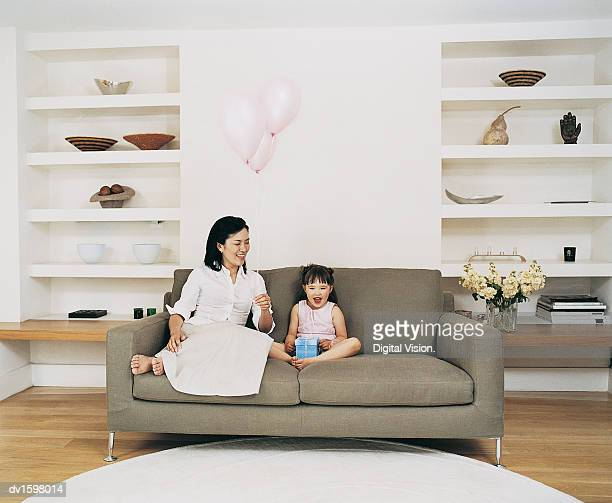 Mother and Daughter Sitting on a Sofa Holding Balloons and a Gift in Their Living Room