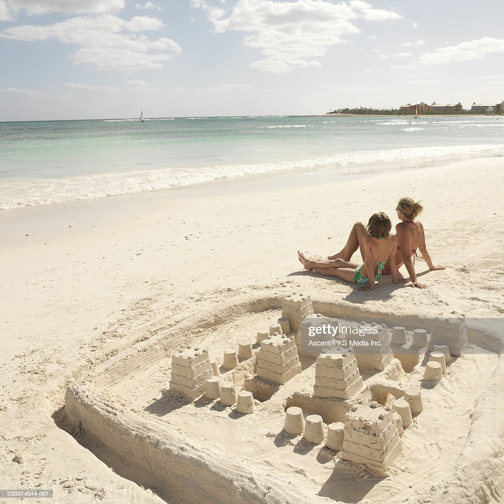 Mother and daughter (9-11) sitting on beach near sand castle : Stock Photo