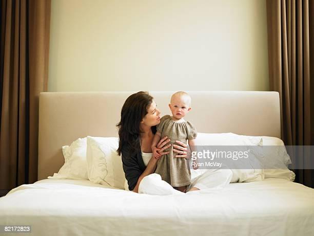 Mãe e filha sentada na cama